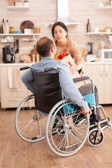 Żona zabierająca torbę na zakupy od niepełnosprawnego męża na wózku inwalidzkim po przybyciu z supermarketu w kuchni. niepełnosprawny, sparaliżowany, niepełnosprawny mężczyzna z niepełnosprawnością chodu, integrujący się po wypadku.