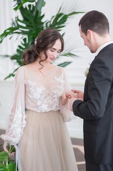 Żonaty, śliczny, noszący obrączkę z brylantem. państwo młodzi w ceremonii ślubnej