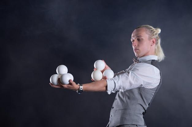 Żongler ubrany w garnitur jak biznesmen z białymi kulkami