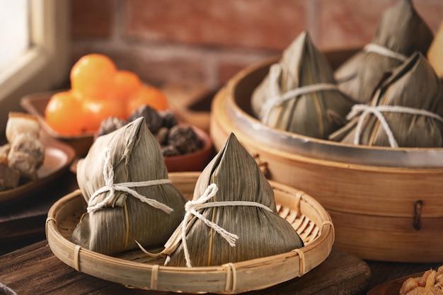 Zongzi chińskie knedle ryżowe zongzi w parowcu na drewnianym stole na święto smoczych łodzi