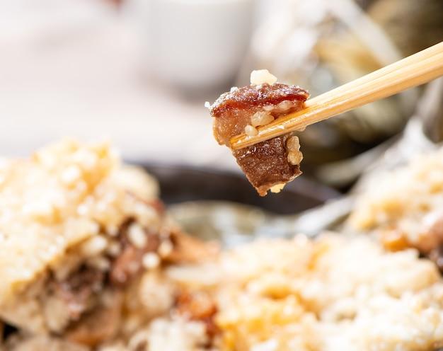 Zongzi (kluska ryżowa) z filiżanką herbaty na drewnianym stole na święto smoczych łodzi