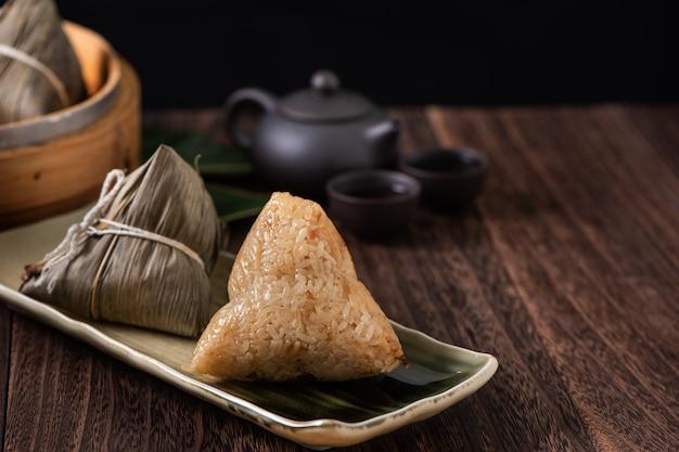 Zongzi. kluski ryżowe na chiński tradycyjny festiwal smoczych łodzi (festiwal duanwu) na tle ciemnego drewnianego stołu.