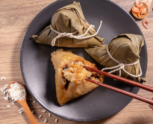 Zongzi, kobieta jedząca gotowane na parze kluski ryżowe na drewnianym stole, jedzenie w koncepcji festiwalu duanwu smoczej łodzi, zbliżenie, kopia przestrzeń, widok z góry, leżenie na płasko