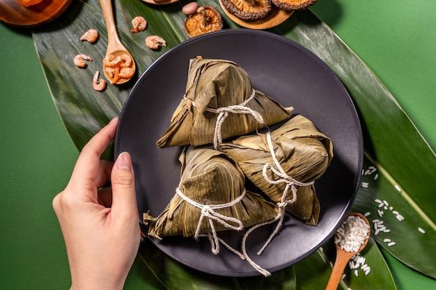 Zongzi, kobieta jedząca gotowane na parze kluski ryżowe na zielonym tle stołu, jedzenie w koncepcji festiwalu duanwu smoczej łodzi, zbliżenie, kopia przestrzeń, widok z góry, leżenie na płasko