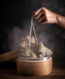 Zongzi, kobieta zamierza zjeść kluskę ryżową na parze na drewnianym stole, słynne smaczne jedzenie w koncepcji projektu dragon boat festival duanwu, zbliżenie, kopia przestrzeń