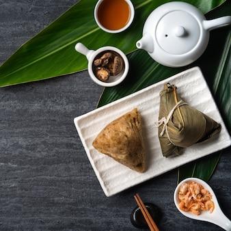 Zongzi. ryż kluska widok z góry koncepcja projektowa dla chińskiego tradycyjnego festiwalu dragon boat (duanwu festival) na ciemnym czarnym tle łupków.