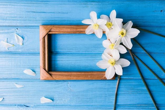 Żonkile z drewnianą ramką na niebieskim tle