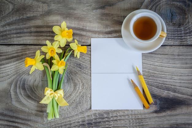 Żonkile z kartą i filiżanką herbaty. kartka z życzeniami. szczęśliwy dzień matki, dzień kobiet lub urodziny. minimalizm, widok z góry, miejsce na tekst.