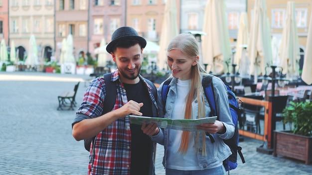 Zoom strzał turystów trzymających mapę i uśmiechających się do kamery. stoją na dużym rynku starego europejskiego miasta.