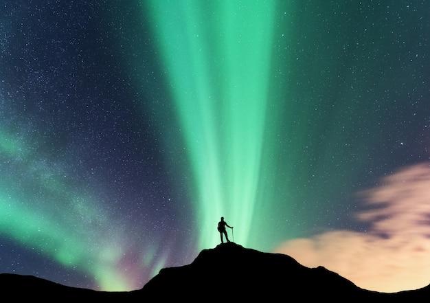 Zorza i sylwetka kobiety stojącej na szczycie góry