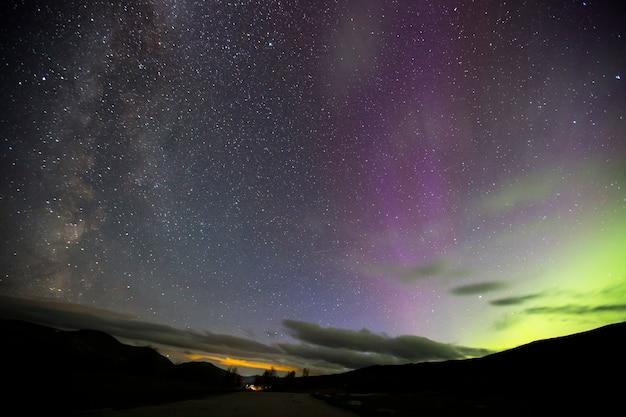 Zorza polarna i droga mleczna w parku narodowym dovrefjell w norwegii. europa