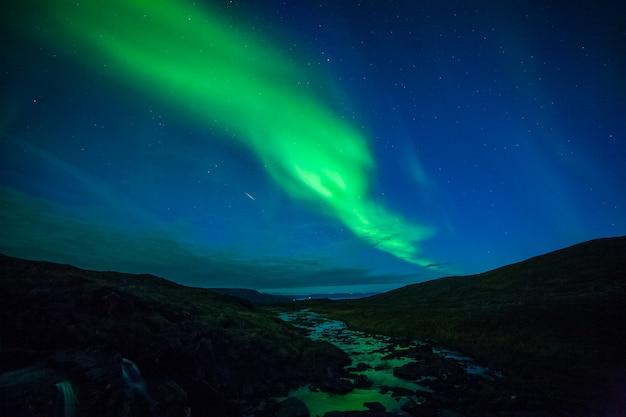 Zorza polarna i rzeka w nordkapp, północny norwegia