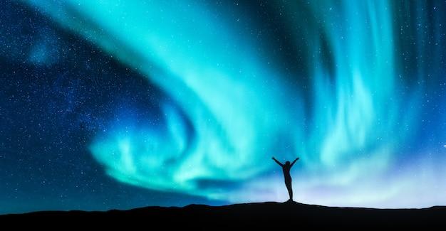 Zorza polarna i sylwetka kobiety stojącej z podniesionymi rękami