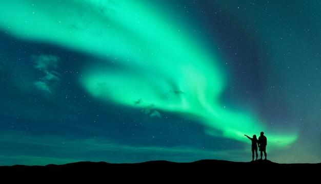 Zorza polarna i sylwetka stojącego mężczyzny i kobiety, którzy wskazują palcem na zorzę polarną