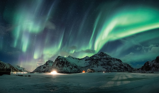 Zorza polarna lub zorza polarna nad śnieżną górą na linii brzegowej