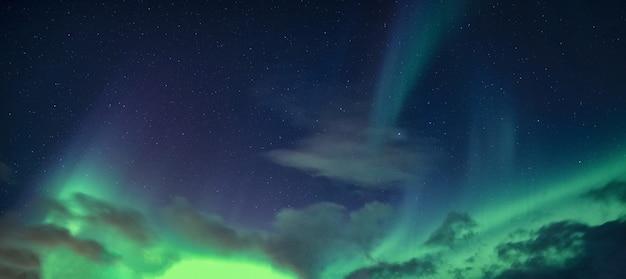 Zorza polarna lub zorza polarna z gwiazdami świecącymi na nocnym niebie na kole podbiegunowym w norwegii