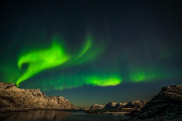 Zorza polarna, morze z odbiciem nieba i zaśnieżone góry. natura, lofoty aurora borealis. lofoty, norwegia.