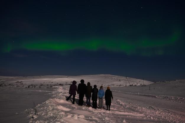 Zorza polarna na cichym polu przed wschodem słońca