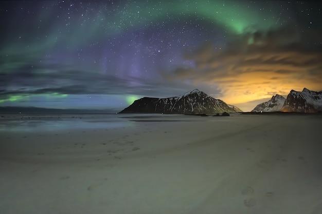 Zorza polarna nad górami na plaży