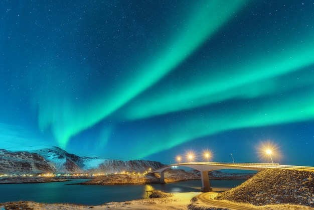 Zorza polarna nad mostem z oświetleniem