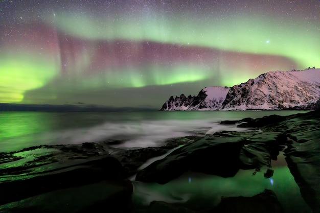 Zorza polarna nad plażą ersfjord. wyspa senja w nocy, europa wyspa senja w regionie troms w północnej norwegii. strzał z długim czasem naświetlania.