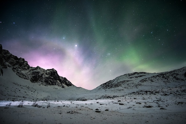 Zorza polarna ze wschodem słońca świecącym nad pasmem górskim na nocnym niebie w zimie