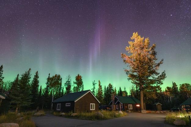 Zorza polarna, zorza polarna nad drewnianą chatą w parku narodowym w jasper
