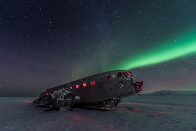 Zorza polarna zorzy polarnej nad samolotowym wrakiem w iceland