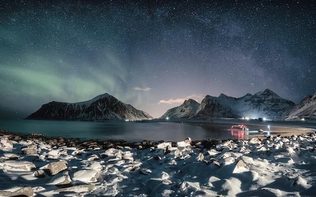 Zorzy borealis z mleczną drogą nad śnieżną górą