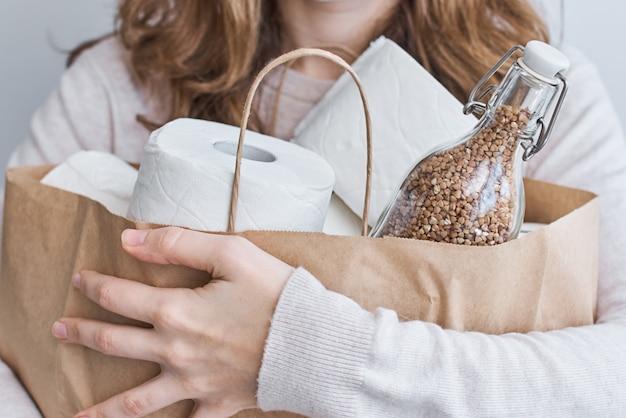 Zostań w domu dzięki koncepcji ochrony covid-19. kobieta trzymać torbę na zakupy z papierem toaletowym i gryki