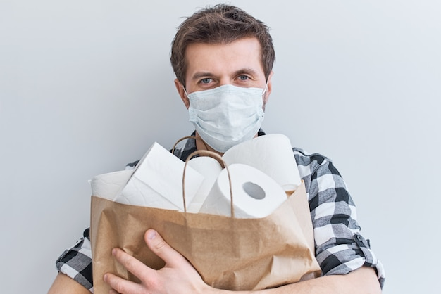 Zostań w domu dzięki koncepcji ochrony covid-19. mężczyzna w masce ochronnej trzyma torbę na zakupy z rolkami papieru toaletowego