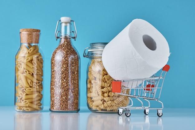 Zostań w domu dzięki koncepcji ochrony covid-19. rolka papieru toaletowego w wózek na zakupy i produsts na niebieskim tle