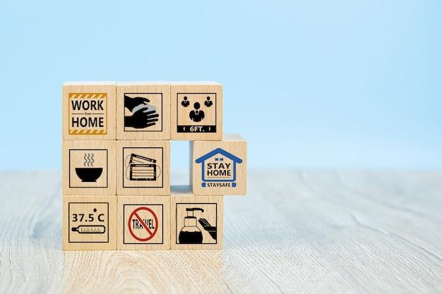 Zostań w domu i ikona zapobiegania covid-19 na drewnianym bloku zabawek.