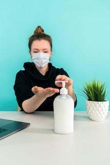 Zostań w domu i umyj ręce. kobieta siedzi przy biurku z mydłem i laptopem.