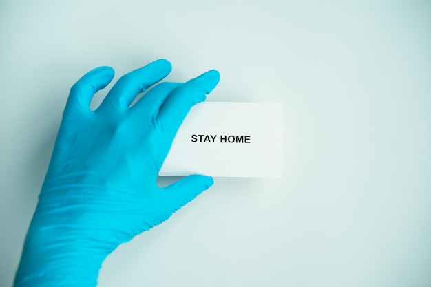 Zostań w domu i zdrowo, aby zapobiec kampanii rozprzestrzeniania się covid-19, tekst na papierze z lekarzem w niebieskich rękawiczkach, dystans społeczny