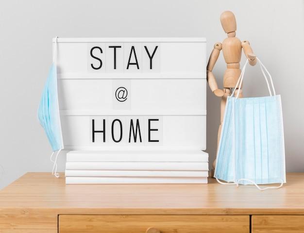 Zostań w domu napis z drewnianym manekinem i maskami medycznymi
