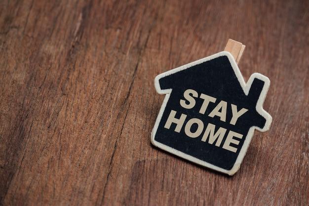 Zostań w domu, rodzinne motywacyjne cytaty, aby zachować bezpieczeństwo w domu przed wybuchem choroby. tekst z drewnianym domem.