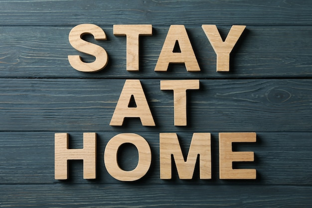 Zostań w domu z drewnianych liter na powierzchni drewna. kwarantanna