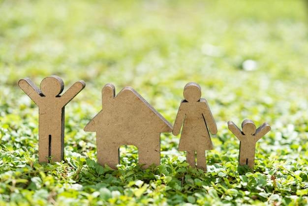 Zostań w domu zachowaj bezpieczeństwo dzięki modelowi domu i rodziny na świeżej zielonej trawie w porannym świetle słonecznym
