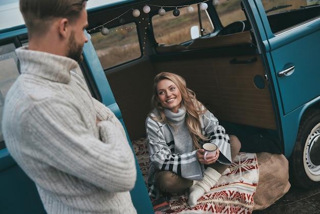 Zostaw wszystkie swoje zmartwienia za sobą! piękna młoda kobieta patrząc na swojego chłopaka i uśmiechając się siedząc w niebieskim mini vanie w stylu retro