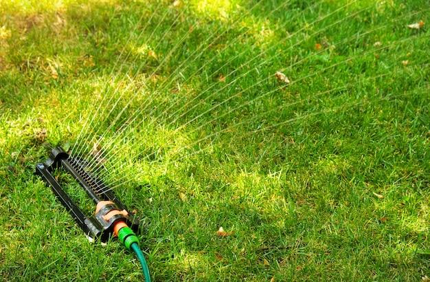 Zraszacz do trawnika rozpryskuje wodę na zielonej trawie. system irygacyjny. podświetlenie