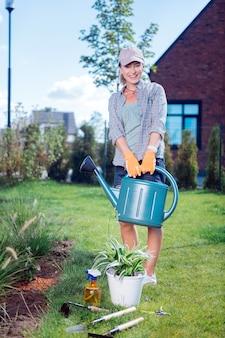 Zraszacz ogrodowy. młody rozpromieniony ogrodnik ubrany w wygodne ubranie trzymający zraszacz ogrodowy podczas podlewania roślin