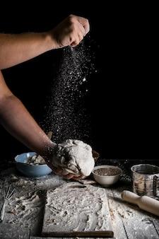 Zraszanie kawałka ciasta mąką pszenną
