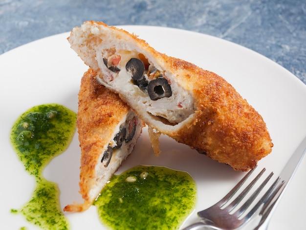 Zraza z kurczaka faszerowana pomidorami, serem i oliwkami. ścieśniać