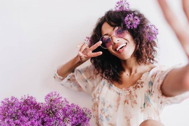 Zrelaksowana afrykańska dziewczyna robi sobie zdjęcie z fioletowymi sojusznikami. wewnątrz zdjęcie fascynującej kręconej modelki w okularach przeciwsłonecznych.