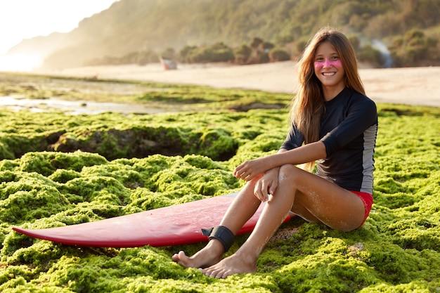 Zrelaksowana, beztroska kobieta o wesołym wyrazie, ubrana w strój kąpielowy, ma długie włosy, siedzi przy desce surfingowej