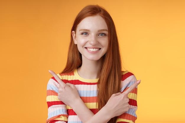 Zrelaksowana, beztroska, pewna siebie, młoda, pomocna ruda dziewczyna pokazuje wybory wskazując skrzyżowanymi rękami w lewo w prawo różne kierunki wybierz warianty dają wiele możliwości, uśmiechając się pomarańczowym tle.