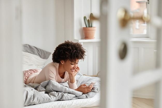 Zrelaksowana ciemnoskóra afrykanka leży na wygodnym łóżku, używa nowoczesnego gadżetu do komunikacji online, ma czarujący uśmiech na twarzy
