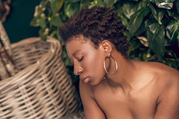 Zrelaksowana ciemnoskóra młoda kobieta w salonie spa