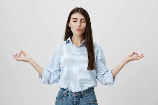 Zrelaksowana, cierpliwa atrakcyjna bizneswoman medytuje z zamkniętymi oczami